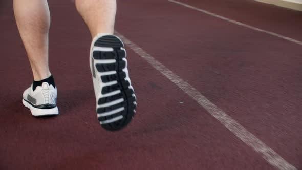 Male Legs in Sport Sneakers Running on Racetrack in Gym Hall