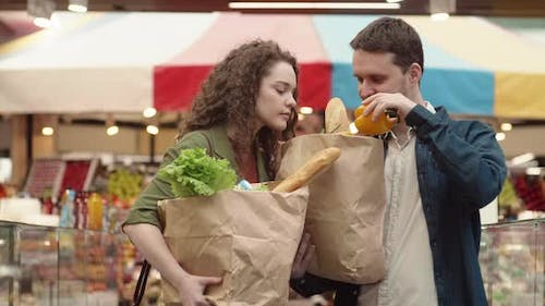 Man and Woman Shopping in Grocery Market