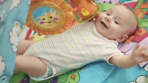 Joyful Baby Lying on Colorful Mat. Happy Infant Playing on Developing Mat