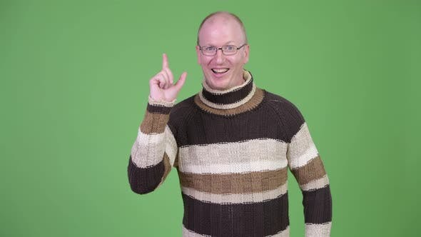 Thumbnail for Happy Mature Bald Man with Turtleneck Sweater Pointing Up