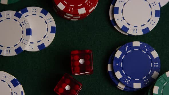 Rotating shot of poker cards and poker chips on a green felt surface - POKER 028