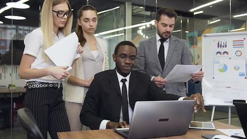 African American Businessman which Showing to His Considerate Purposeful Male and Female