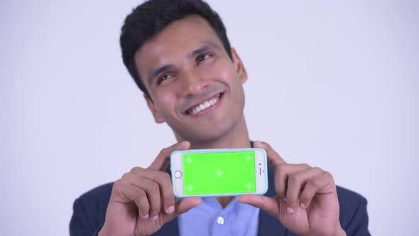 Thumbnail for Face of Happy Young Indian Businessman Thinking While Showing Phone