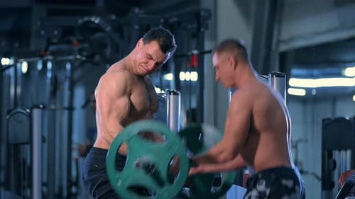 Bodybuilder Doing an Exercise with a Barbell in the Gym