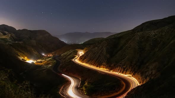 Night time lapse of a road winding through the mountains