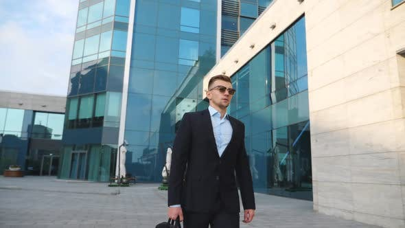 Young Businessman in a Black Suit with Briefcase Walking Along Modern Office Building. Confident