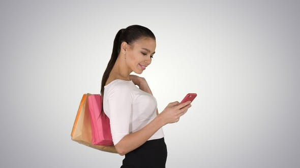 Thumbnail for Beautiful young woman using a mobile phone walking and