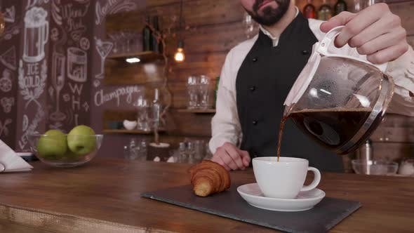 Thumbnail for Barista Man While He Holds a Pitcher and Pour Coffee in a Empty Cup