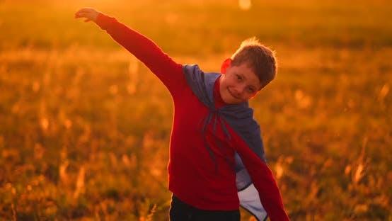 Thumbnail for Ein Kind im Kostüm eines Superhelden in einem roten Umhang läuft über den grünen Rasen vor dem Hintergrund