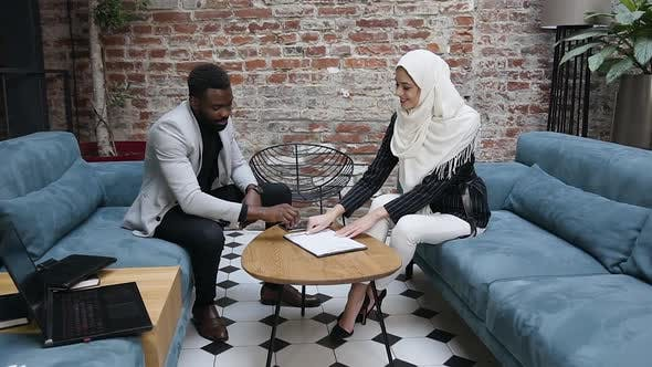 Thumbnail for Muslim Businesswoman in Hijab Signing the Agreement with Bearded African American Business Partner