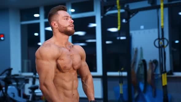 Modellaufbauhersteller posiert vor der Kamera und zeigt perfekte Bauchmuskeln und starken Körper.