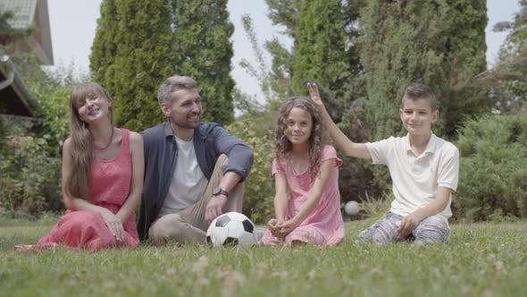 Thumbnail for Portrait Happy Family Sitting on the Grass in the Garden Together Mother Father Son and Daughter