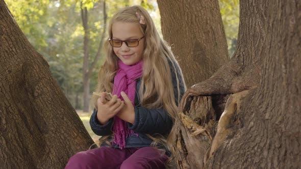 Thumbnail for Junge lächelnd kaukasische teenager-Mädchen in photochrome Brille halten Geld und zeigen Sieg