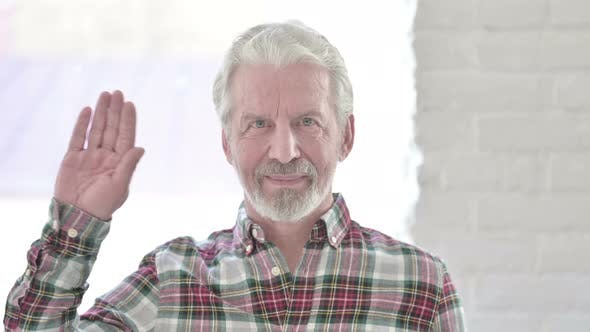 Portrait of Casual Old Man Waving at the Camera