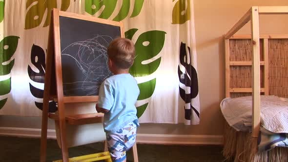Thumbnail for Young two-year-old writing with chalk on board