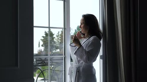 Woman in Bathrobe Talking By Phone at Hotel Room