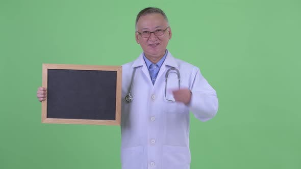 Thumbnail for Happy Mature Japanese Man Doctor Holding Blackboard and Giving Thumbs Up
