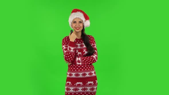 Sweety Girl in Santa Claus Hat with TV Remote in Her Hand, Switching on TV. Green Screen