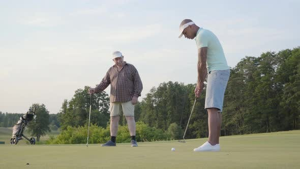 Cover Image for Mature Caucasian Man and Young Middle Eastern Man Playing Golf on the Golf Field