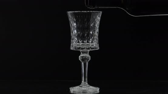 Rose Wine. Red Wine Pour in Wine Glass Over Black Background. Silhouette