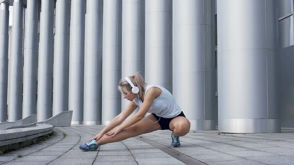 Thumbnail for Beautiful female elegantly stretches leg muscles before jogging, warmup routine