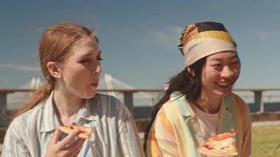 Young Women Enjoying Pizza Outdoors