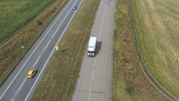 Thumbnail for Aerial View of Truck with Cargo Trailer Driving on Empty Road and Transporting Goods. Flying Over