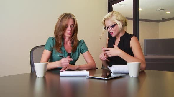Thumbnail for Two businesswomen writing notes