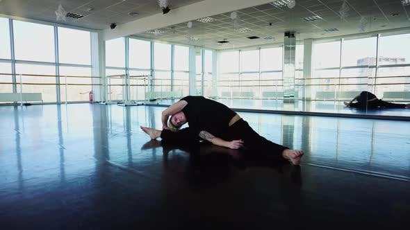 Ballet Dancer in Sportswear Doing Stretching Exercises to Keep Fit
