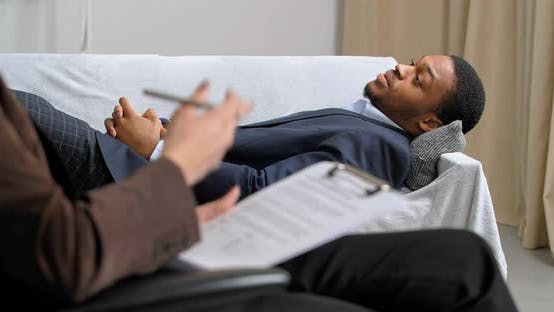 Afro American Business Man Lies on Couch in Office of Psychologist Consults with Psychiatrist Going