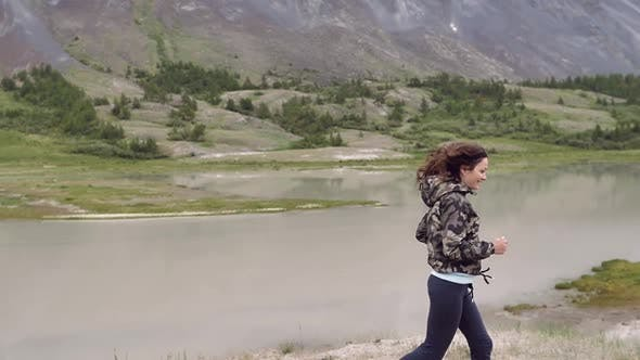 Young Woman on the Background of the Mountains Runs and Dances. Traveler