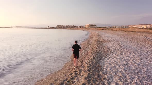 Thumbnail for Young athlete runner man with fit strong body training on beautiful sunset at beach