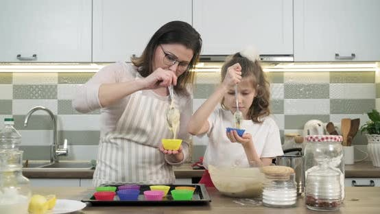 Thumbnail for Mother and Daughter Child 9, 10 Years Old Preparing Cupcakes Together at Home in Kitchen