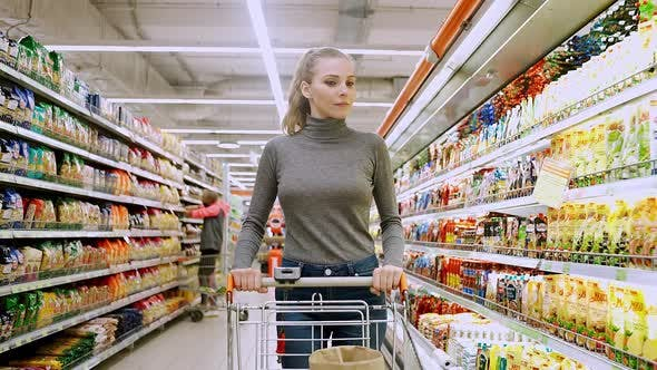 Young Female Walks Between the Shelves in a Grocery Store Visiting a Supermarket a Woman Walks with