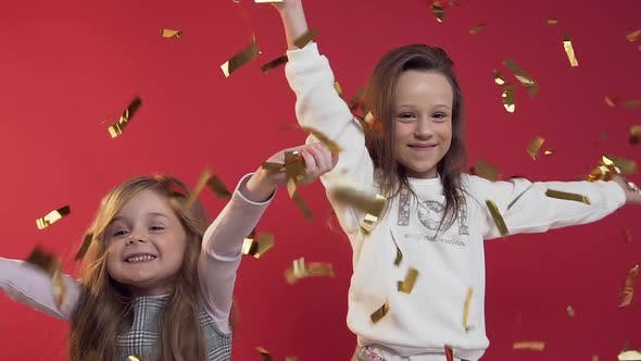 Thumbnail for Pretty Little Girls Throwing Golden Confetti on the Red Background