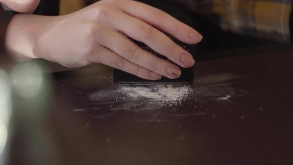 Thumbnail for Hand of Young Drug Addict Woman Making Cocaine Line with Black Credit Card on Wooden Surface at Home