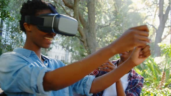 Twin sisters experiencing VR headset in the park 4k