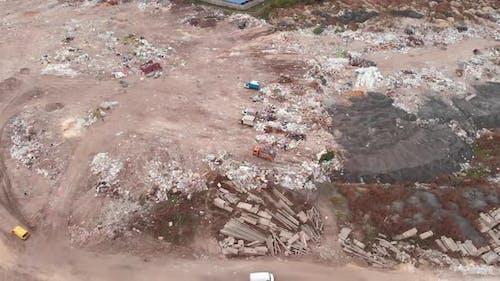 Garbage dump. Bulldozer is pushing debris on field. Construction waste