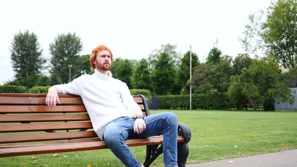 Thumbnail for Waiting Man Sitting in Park on Bench, Red Hairs and Beard