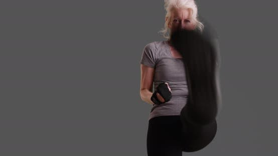 Thumbnail for Slowmo of focused mature woman shadowboxing on gray background with copyspace