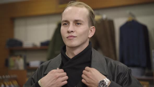 Close-up of Confident Handsome Young Man Trying on New Leather Jacket in Shop. Portrait of Smiling