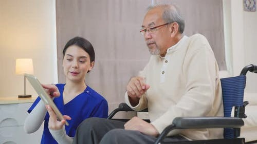 Asian Senior elderly male patient talking to physician nurse at nursing home care.