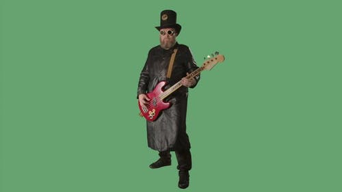 A Bearded Man in a Long Leather Coat an Irish Style Hat and Original Glasses Plays the Red Guitar