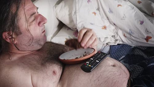 Fat Man Eating In Bed Watching Television 7