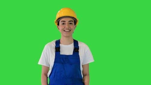 Young Woman in Yellow Hardhat Walking on a Green Screen Chroma Key