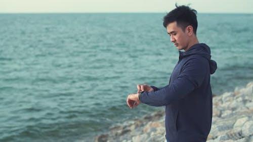 Attractive fitness man wearing sportswear standing outdoors.