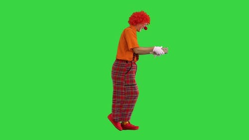 A Happy Male Clown Holding a Present and Walking on a Green Screen Chroma Key