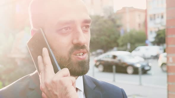 Thumbnail for Portrait of Business Person Talking on the Phone with the Sun Behind Him