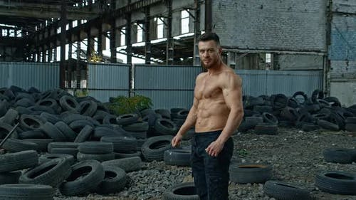 Handsome muscular man posing outside. Muscular man standing against old tyres background