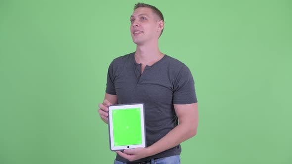 Cover Image for Happy Young Man Thinking While Showing Digital Tablet